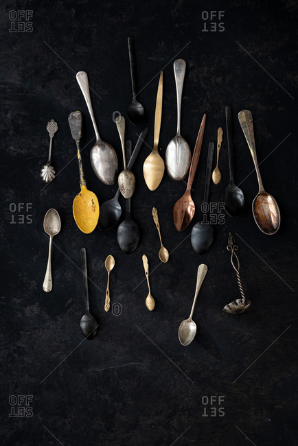 From above of set of various old fashioned spoons placed on black background in studio