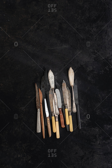From above of collection of vintage knives placed on black background in studio