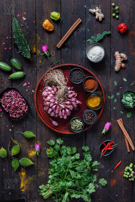 Top view of various seasonings and greenery arranged on wooden table in kitchen