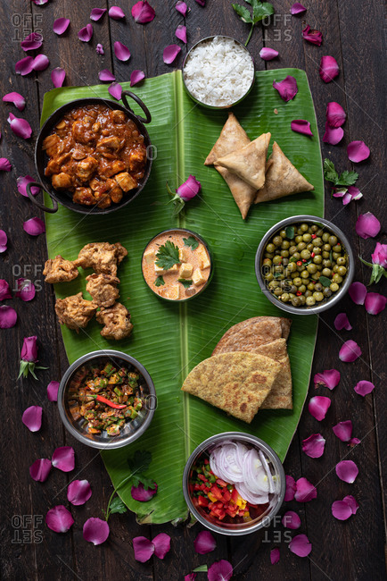 From above of assorted dishes of Indian cuisine arranged on huge banana leaf for celebrating Onam Sadhya