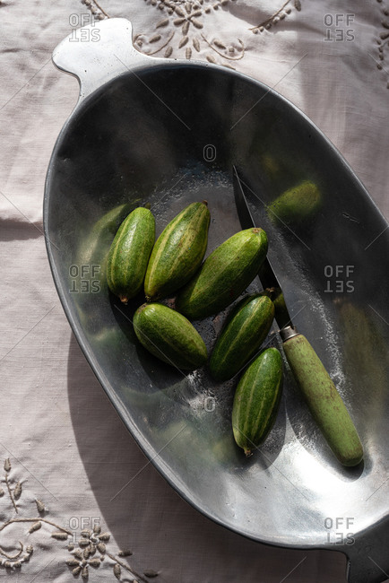 From above of ripe delicious cucumbers in metal bowl placed on rustic table in kitchen
