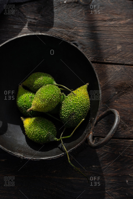 From above of ripe green spiny gourds in bowl placed on rusty wooden table in kitchen