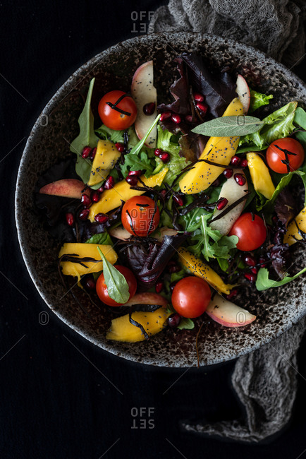 Top view of tasty nourishing salad with various ripe ingredients served in bowl on black background