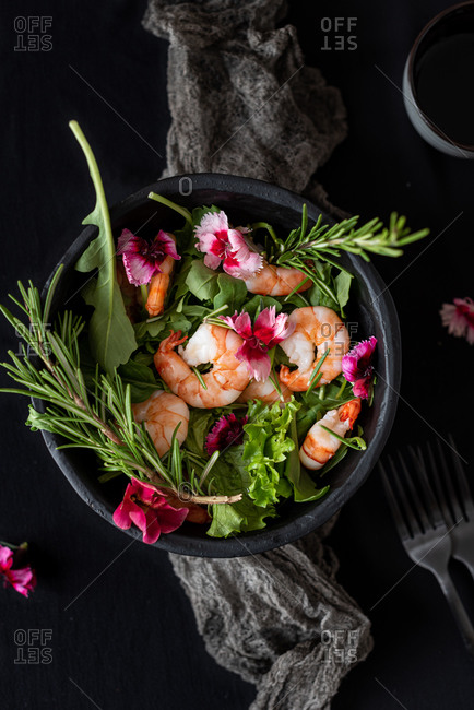 Top view of appetizing salad with shrimps and various green herbs garnished with flowers in bowl placed on table near forks and soy sauce