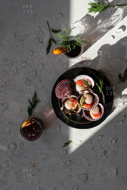 Top view of tasty oriental dish made of clams with herbs served on table with glasses of refreshing cocktails garnished with dried oranges