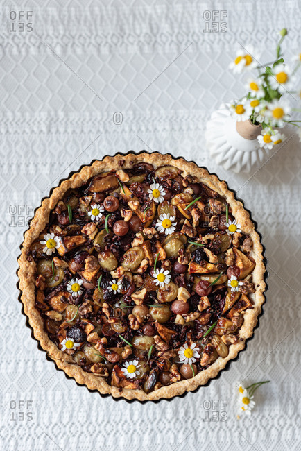 Top view of sweet yummy tart with various dried berries served on table with bouquet of chamomile flowers in rustic kitchen