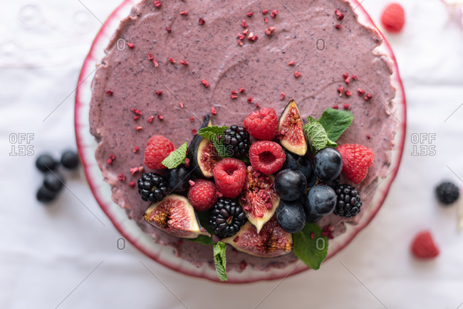 From above of tasty healthy cake decorated with fresh berries and fruits and served on table