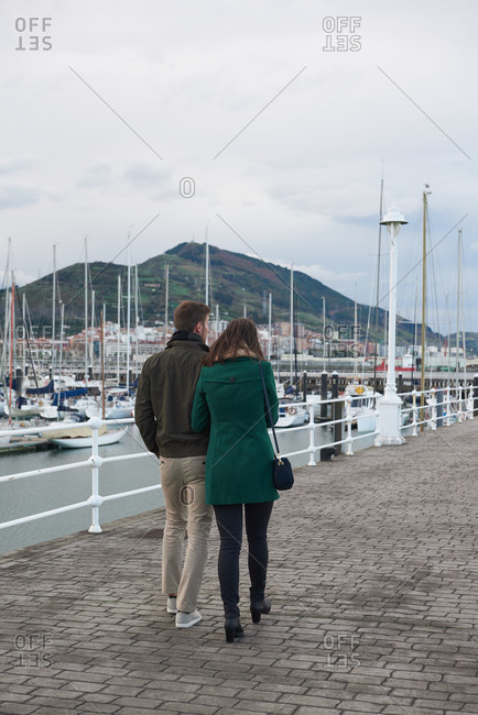 Back view of couple holding hands and walking along embankment in port near sea while enjoying stroll in autumn together