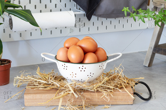 Heap of brown chicken eggs in white colander placed on table in cozy home kitchen