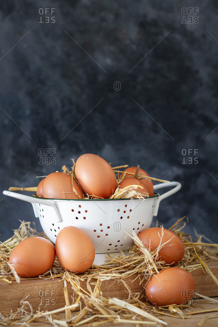 Composition with brown chicken eggs in white bowl placed on wooden board with dry hay against dark background