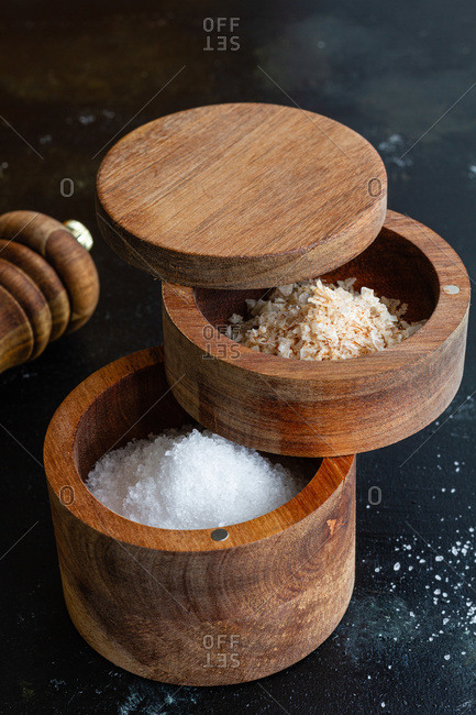 High angle of assorted types of salt in wooden jars placed on table with pepper mill in kitchen
