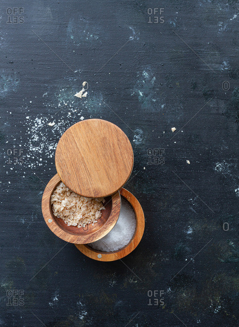 Top view of assorted types of salt in wooden jars placed on table with pepper mill in kitchen