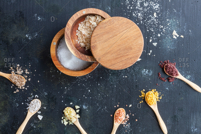 Top view of various types of salt in wooden jars and spoons placed on black table in kitchen