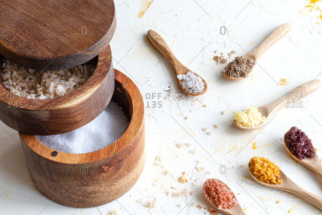 Top view of various types of salt in wooden jars and spoons placed on white table in kitchen