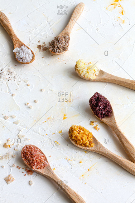 Top view of various types of salt in wooden spoons placed on white table in kitchen