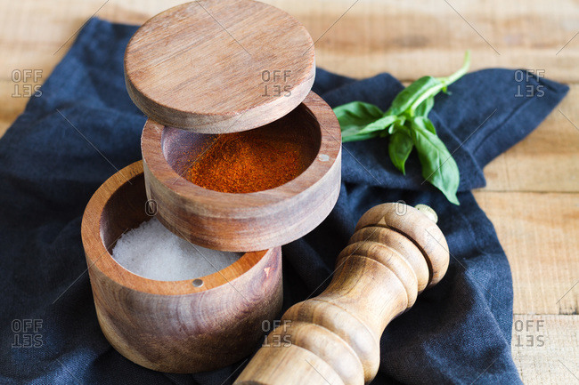 High angle of wooden pepper mill and jars with salt and aromatic paprika arranged on napkin on table in domestic kitchen