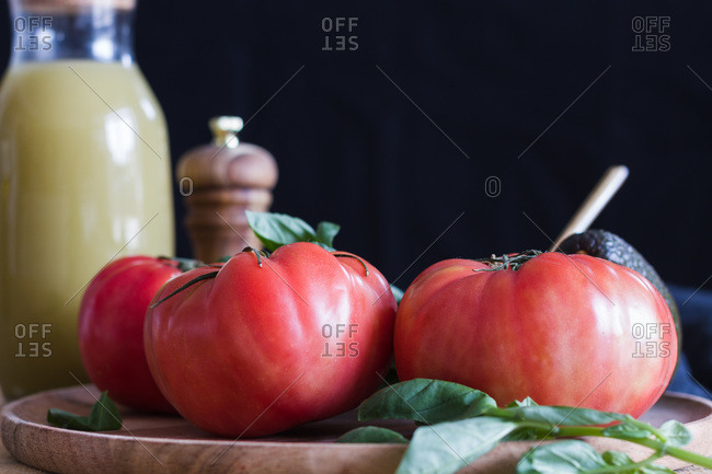 Ripe red tomatoes placed on wooden cutting board with basil and vegetables in kitchen