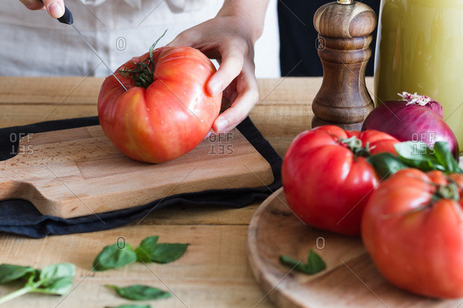 Unrecognizable crop person chopping fresh tomatoes on wooden cutting board while preparing ingredients for tomato soup in kitchen