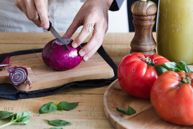 Unrecognizable crop person chopping fresh onion on wooden cutting board while preparing ingredients for tomato soup in kitchen