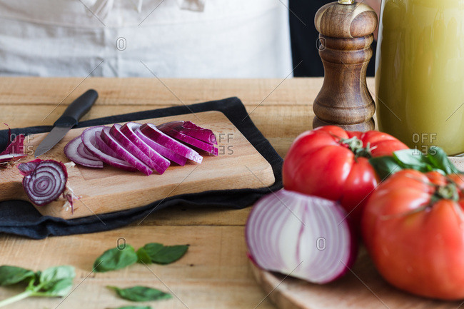 Slices of fresh onion on wooden cutting board while with ingredients for tomato soup in kitchen