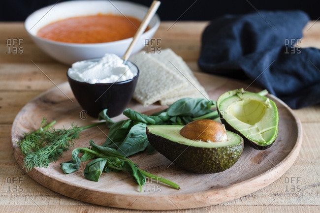 Halves of fresh avocado placed on table with portion of homemade tomato soup and green herbs