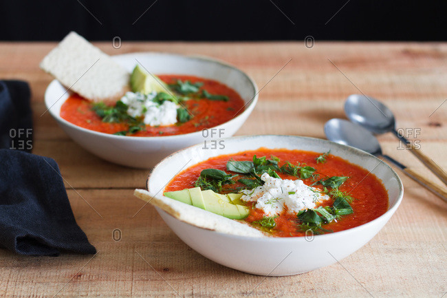 Portion of homemade tomato soup in bowl placed on wooden table