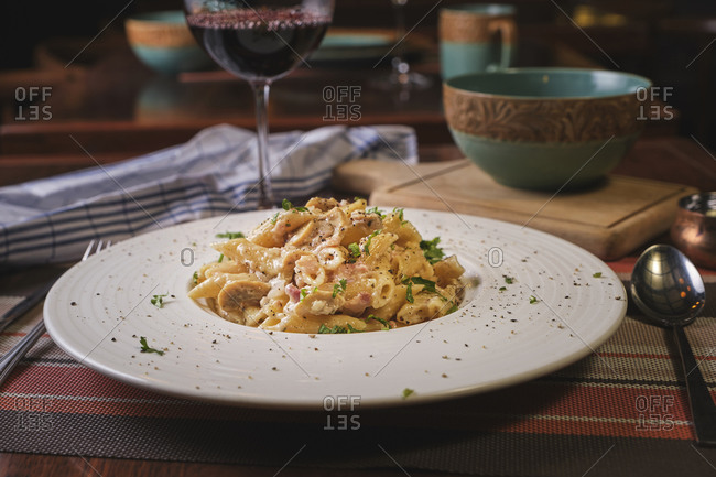 Beautiful dish of Penne carbonara on wooden table.