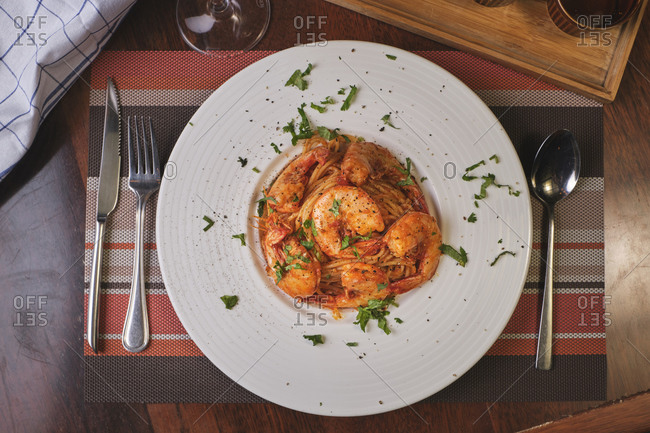 Beautiful dish of spaghetti  with prawns on wooden table.