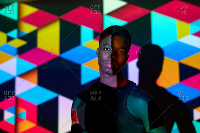 Calm black male model standing in dark studio illuminated by colorful neon light projection in shape of cubes and looking at camera