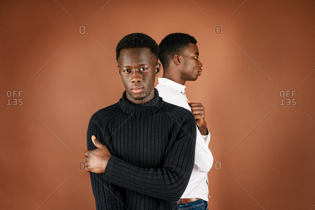 Back view of ethnic man standing in studio with African American male looking confidently at camera on brown background