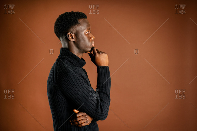 Side view of pensive African American male rubbing chin and leaning on hand while standing on brown background in studio and looking away