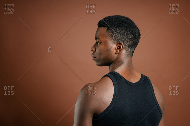 Thoughtful black man in casual outfit in studio