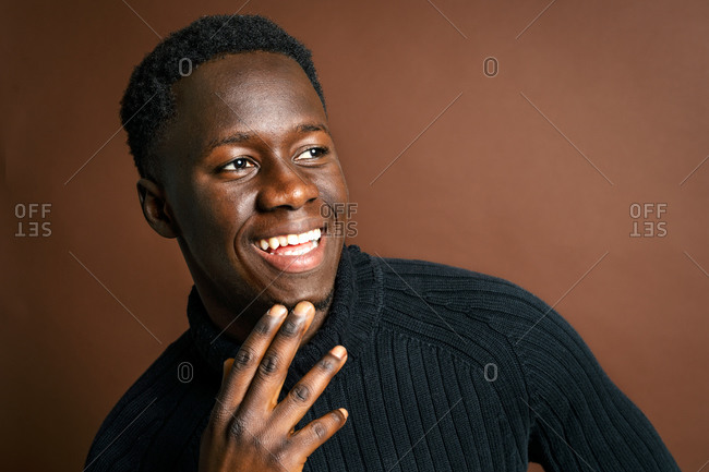 Side view African American male rubbing chin and leaning on hand while standing on brown background in studio and looking away