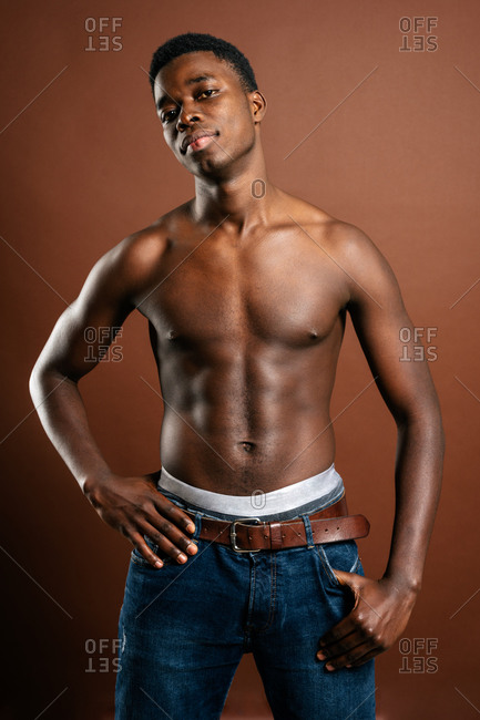 Confident African American young male with muscular naked torso standing in trendy jeans with hand on waist on brown background in studio and looking at camera