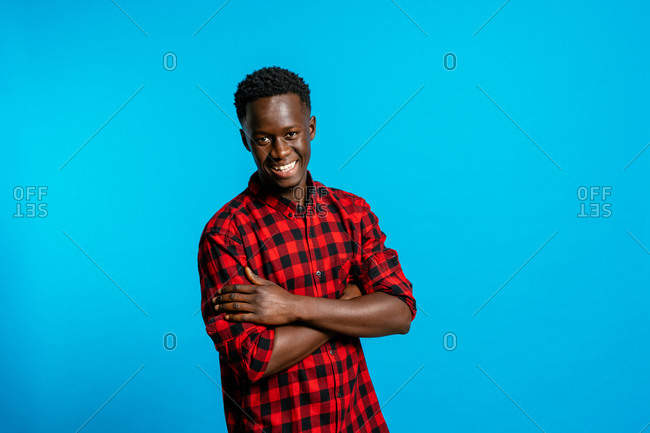 Delighted handsome African American male wearing classic shirt standing on brown background in studio and looking at camera