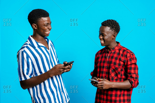 Content African American male best friends in trendy clothes browsing smartphones and laughing at jokes while standing on blue background in studio and looking at each other