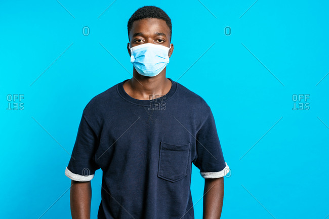 Serious African American male with sterile medical mask while standing on bright blue background in studio and showing concept of coronavirus prevention