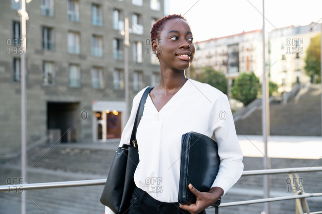 Confident successful positive young black businesswoman with short hairstyle standing near river against modern buildings in downtown