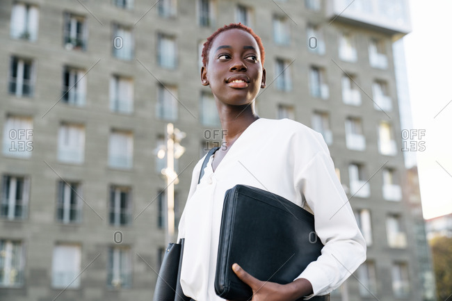 Low angle side view of confident smiling young African American female manager in elegant white blouse carrying laptop case and looking away while standing near modern urban building