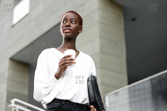 Low angle of positive elegant young black business lady with cup of takeaway coffee standing near modern urban building