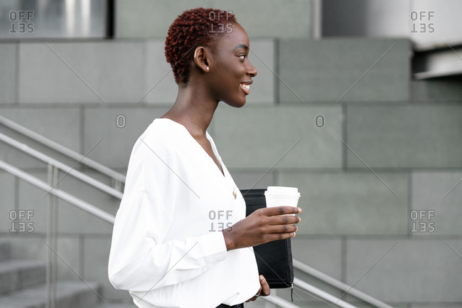 Side view of positive elegant young black business lady with cup of takeaway coffee standing near modern urban building