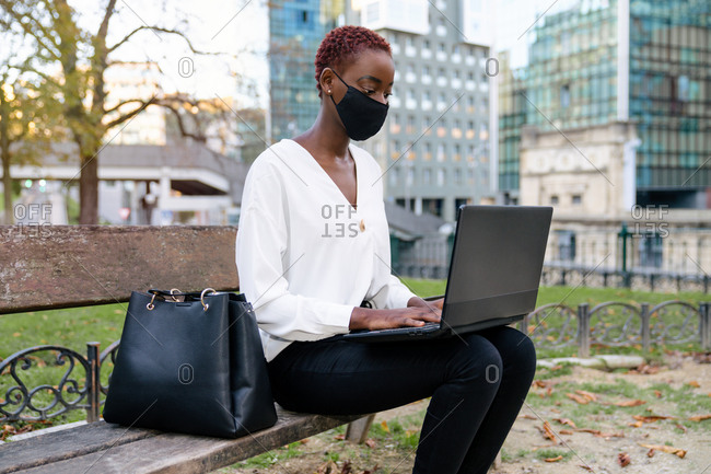 Young African American businesswoman with face mask in elegant clothes sitting on bench and working on laptop against blurred modern urban background