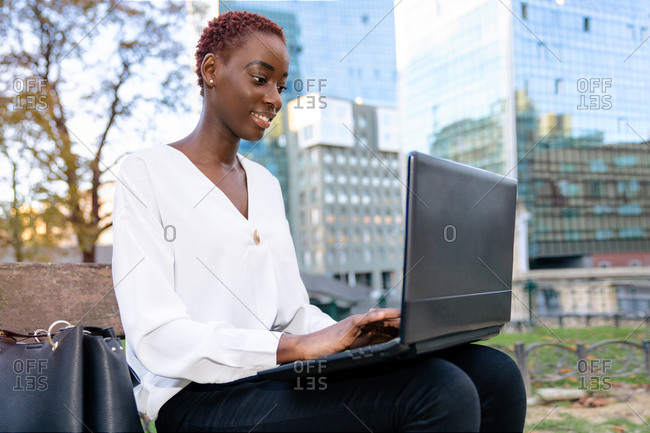 Positive young African American businesswoman in elegant clothes sitting on bench and working on laptop against blurred modern urban background