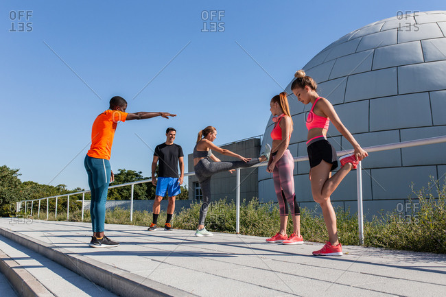 Group of multiethnic sportspeople stretching bodies while warming up before workout in city