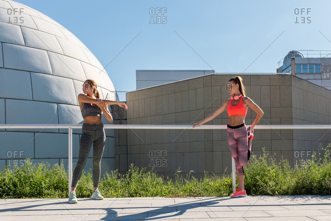 Slim female runners in activewear standing in street and stretching muscles while warming up before workout in city in summer