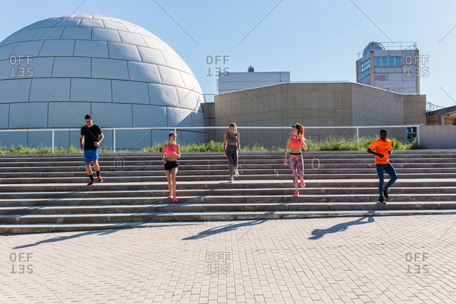 Company of diverse runners running down stairs in city while doing cardio workout together on sunny day in summer
