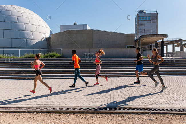 Side view of diverse sportspeople running along street while training together in city on sunny day