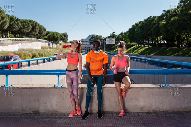 Group of multiracial runners in sportswear standing on street on sunny day during training