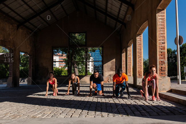 Group of diverse sportspeople standing in crouch start position ready for run during training in urban area of city