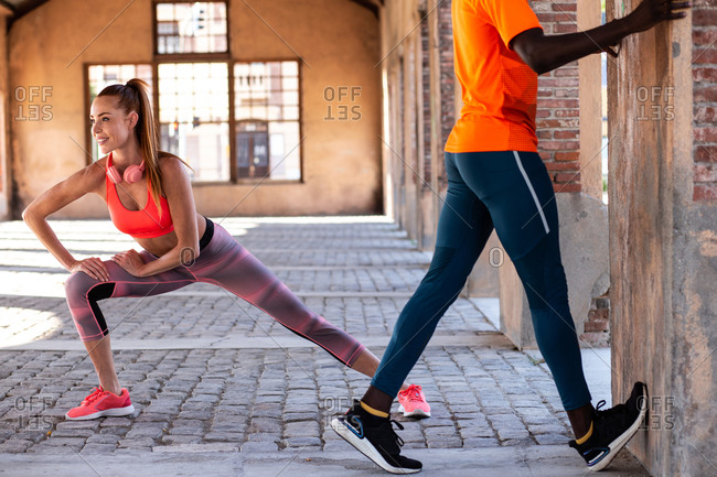 Flexible diverse runners in sportswear doing bends while stretching legs and warming up before workout in city